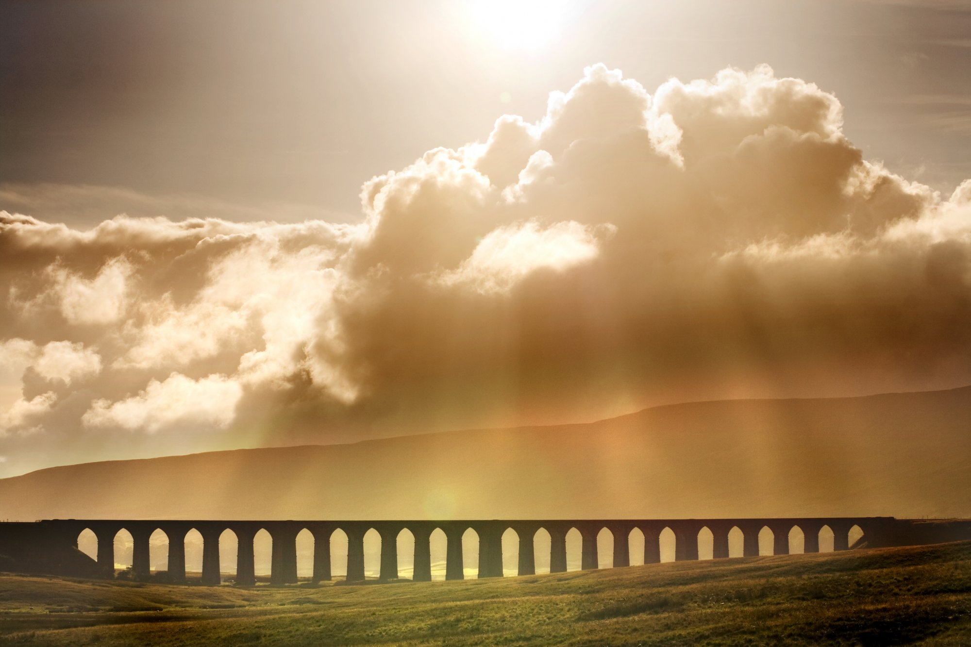 Photo of Ribblehead Viaduct and sunshine streaming through clouds - from wikimedia