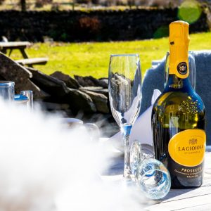 a bottle of prosecco on the table outside middle studfold farm