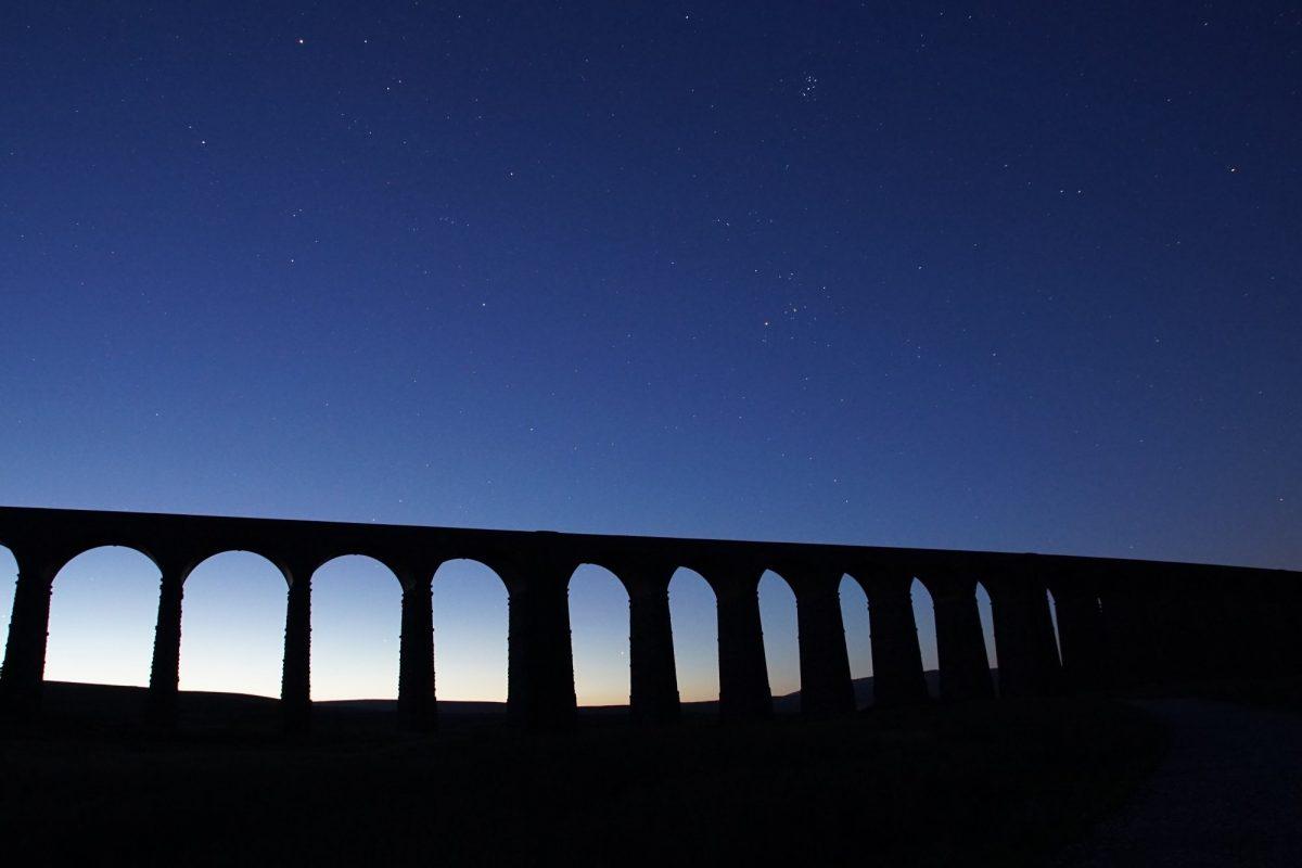 photo of Ribblehead Viaduct silhouette against a dark blu sky
